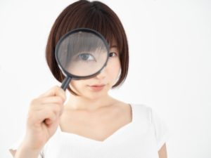 ルーペを覗いている女性の画像